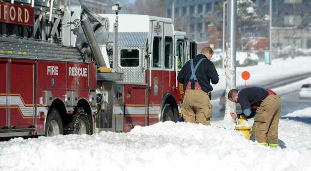 Firefighters dig out a fire hydrant buried by snow in Stamford, Conn., on Saturday, February 9, 2013. Photo: Lindsay Perry / Stamford Advocate
