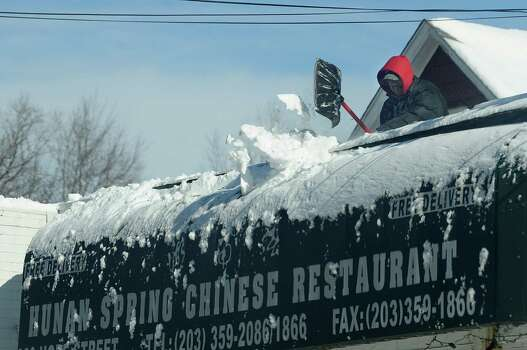 A worker clears the roof of Hunan Spring Chinese restaurant in Stamford, Conn., on Saturday, February 9, 2013. Photo: Lindsay Perry / Stamford Advocate