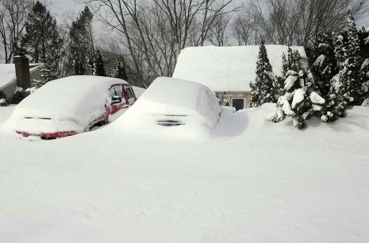 Cars remain buried in snow on Burroughs Rd. in Fairfield, Conn. on Saturady, Feb. 9, 2013. An overnight blizzard dumped over two feet of snow on the area. Photo: Cathy Zuraw / Connecticut Post