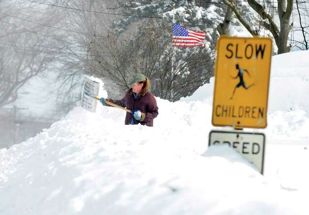 Sandra Pederzini shovels her driveway on Judd St. in Fairfield, Conn. on Saturday, Feb. 9, 2013. Southwestern Connecticut was hit by one of the biggest snowstorms in history, a howling blizzard that dumped up to three feet of snow across the state. Photo: Cathy Zuraw / Connecticut Post