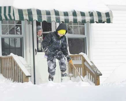Karen Drena watches her son, Calder Waugh jump off the porch into the deep snow on Moritz Place in Fairfield, Conn. on Saturday, Feb. 9, 2013. Southwestern Connecticut was hit by one of the biggest snowstorms in history, a howling blizzard that dumped up to three feet of snow across the state. Photo: Cathy Zuraw / Connecticut Post