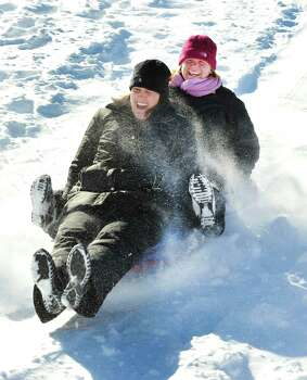 Kim Butera, left, and Erin Williams have fun sledding in the snow behind St. Gregory the Great Church in Danbury Saturday, Feb. 9, 2013. Photo: Michael Duffy / The News-Times