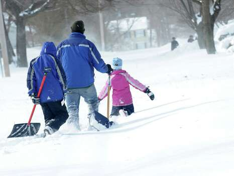 Larry Palaia and his children, Andrew and Cate head down Wilson St. to dig out grandma's driveway in Fairfield, Conn. on Saturday, Feb. 9, 2013. Southwestern Connecticut was hit by one of the biggest snowstorms in history, a howling blizzard that dumped up to three feet of snow across the state. Photo: Cathy Zuraw / Connecticut Post