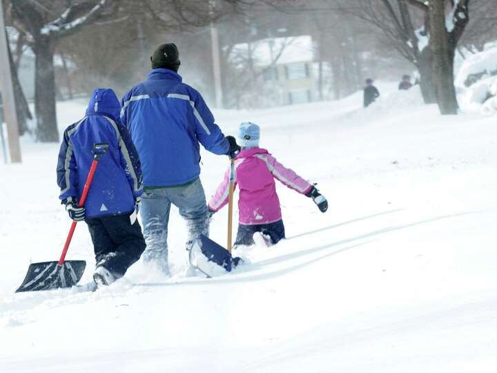Larry Palaia and his children, Andrew and Cate head down Wilson St. to dig out grandma's driveway in