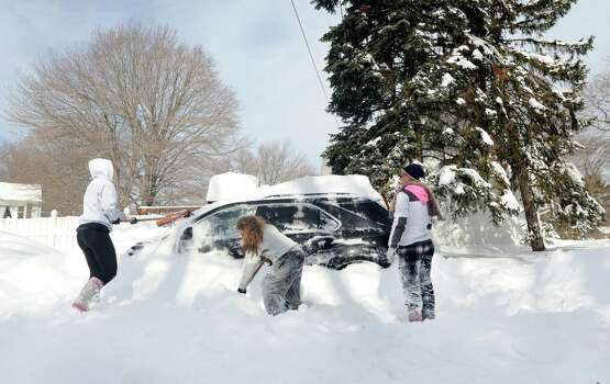Janine Dubois, Tala Malas and Alley Meyer dig out Janine's car parked on Kalan Circle in Fairfield, Conn. on Saturday, Feb. 9, 2013. Southwestern Connecticut was hit by one of the biggest snowstorms in history, a howling blizzard that dumped up to three feet of snow across the state Photo: Cathy Zuraw / Connecticut Post