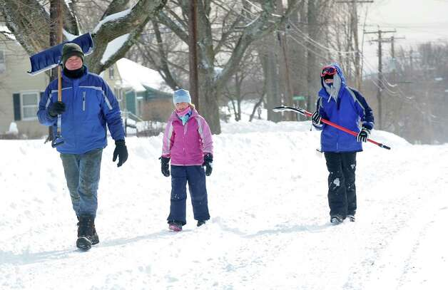Larry Palaia and his children, Cate and Andrew head up High St. to Wilson St. to dig out grandma's driveway in Fairfield, Conn. on Saturday, Feb. 9, 2013. Southwestern Connecticut was hit by one of the biggest snowstorms in history, a howling blizzard that dumped up to three feet of snow across the state. Photo: Cathy Zuraw / Connecticut Post