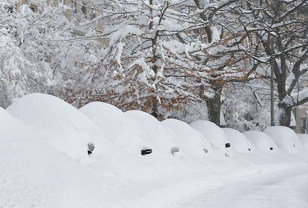 Snow covered vehicles sit on Commonwealth Avenue on February 9, 2013 in the Brighton neighborhood of Boston, Massachusetts. The powerful storm has knocked out power to 650,000 and dumped more than two feet of snow in parts of New England. Photo: Jared Wickerham, Getty Images