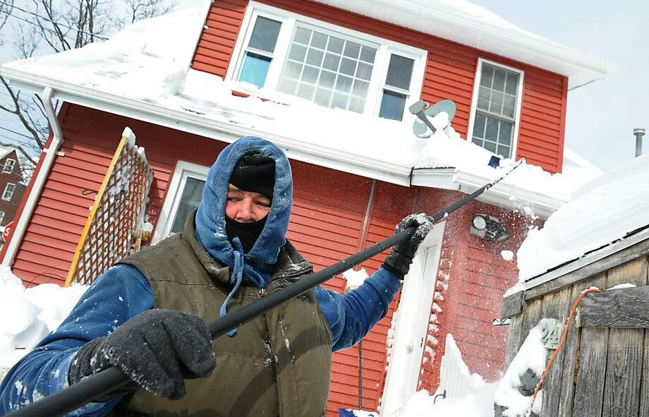 Walter Brennan clears snow from his roof using a roof rake after a blizzard pounded the region in West Haven, Conn. on Saturday February 9, 2013. Photo: Christian Abraham