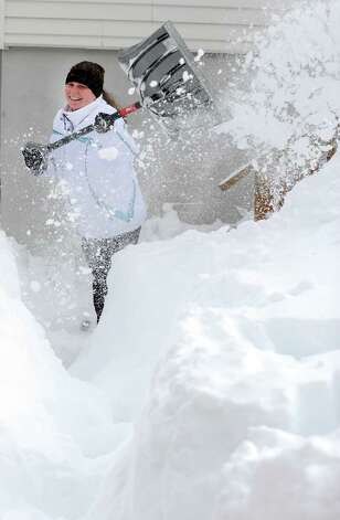 Tania Tchir shovels a path from her house in Derby, Conn. as resident