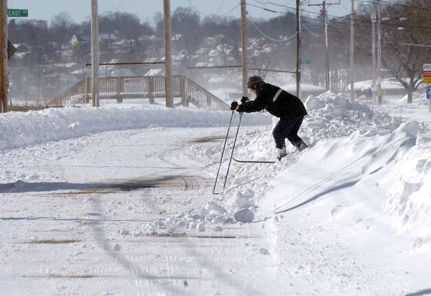 A cross country skier works her way over a snow bank onto Beach Street after a blizzard pounded the region in West Haven, Conn. on Saturday February 9, 2013. Photo: Christian Abraham / Connecticut Post