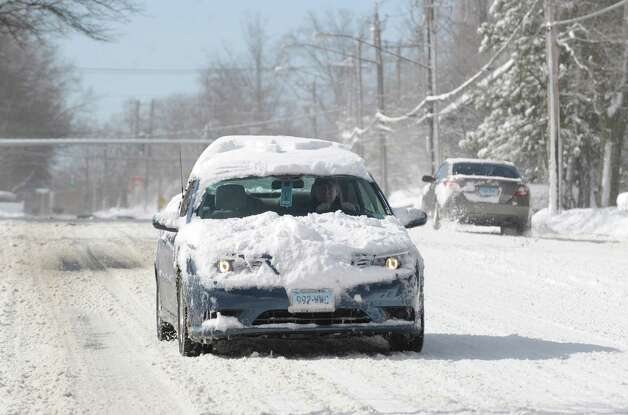 A snow-covered car travels on West Putnam Avenue during the aftermath of the blizzard that hit Greenwich, Conn., Saturday morning, Feb. 9, 2013. Photo: Bob Luckey / Greenwich Time