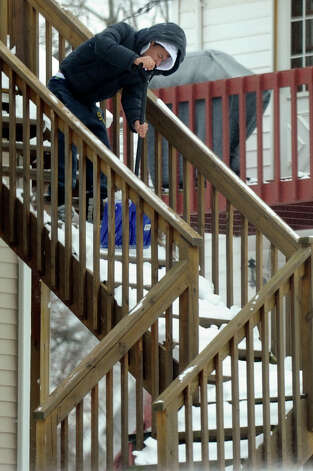 A man clears the steps from his home in Danbury, Conn. Saturday morning, February 9, 2013. A blizzard dumped almost two feet of the snow in the area Friday and Saturday. Photo: Carol Kaliff / The News-Times