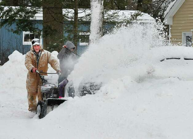 Brian Rosler uses his snowblower to help a neighbor dig out of the snow in Danbury Saturday, Feb. 9, 2013. Photo: Michael Duffy / The News-Times
