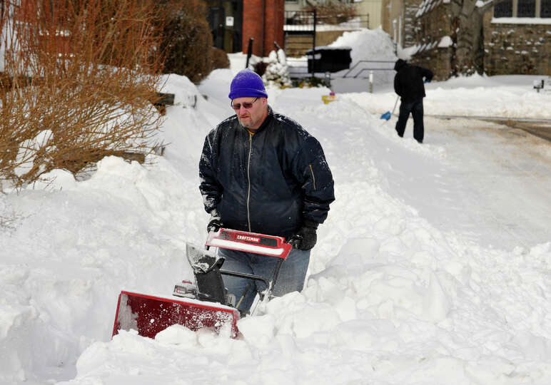 Todd Rogotzke, left, and Charles Scalzo work to remove snow from the sidewalk and a fire hydrant nex