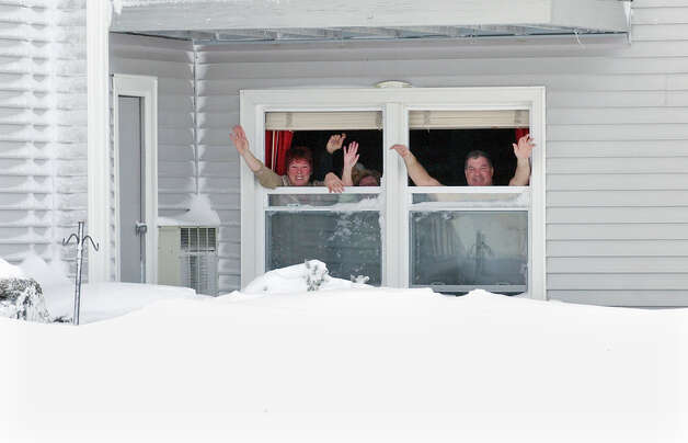 Residents Nancy and Lou Tagliatele waves from their first floor window as they have a blizard party at their home along Beach Street after a blizzard pounded the region in West Haven, Conn. on Saturday February 9, 2013. Photo: Christian Abraham / Connecticut Post