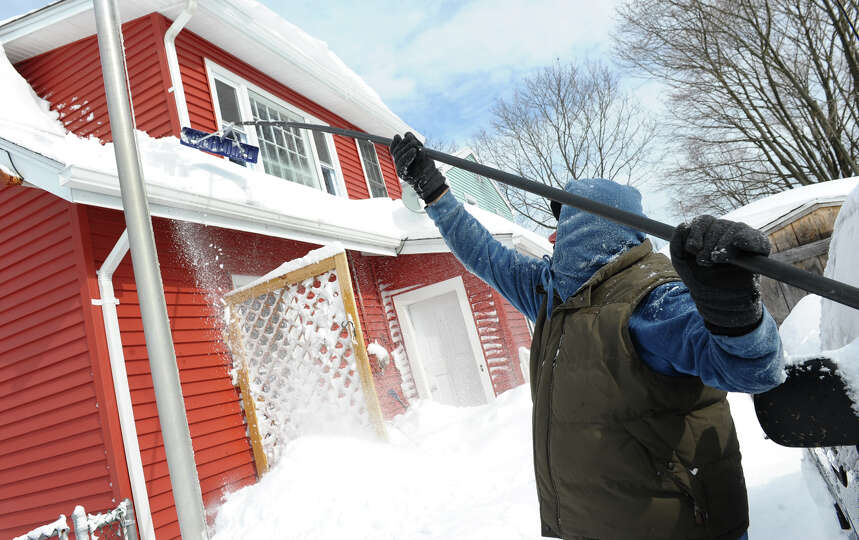Walter Brennan clears snow from his roof using a roof rake after a blizzard pounded the region in We