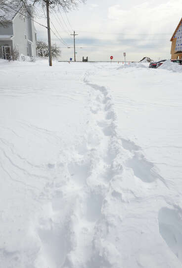Footsteps are the only marks made on a side street after a blizzard pounded the region in West Haven