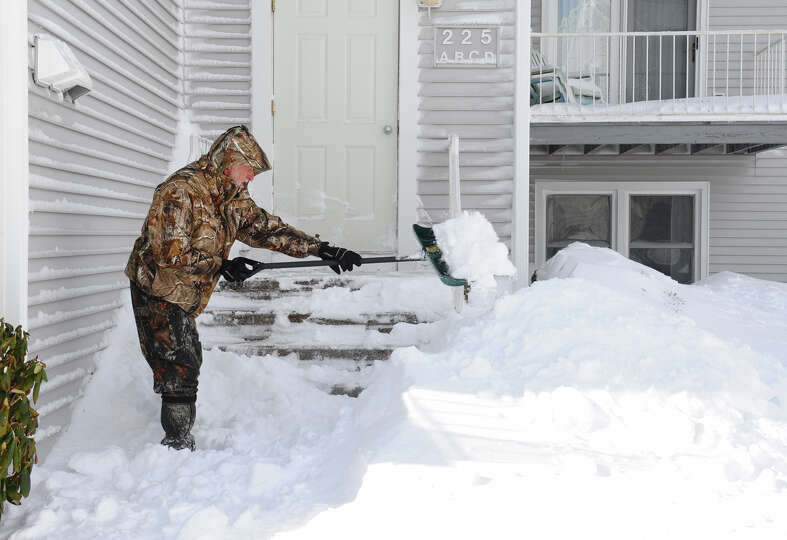 Mike Dunphy shovels his porch at his condo along Beach Street after a blizzard pounded the region in
