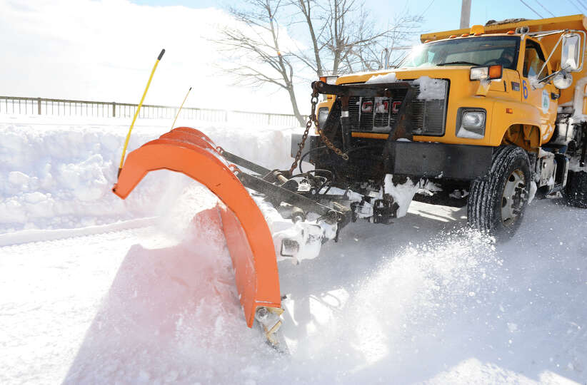A city plow speeds by on Beach Street after a blizzard pounded the region in West Haven, Conn. on Sa