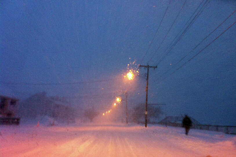 A lone pedestrian walks along Beach Street while a blizzard pounds the region in West Haven, Conn. o