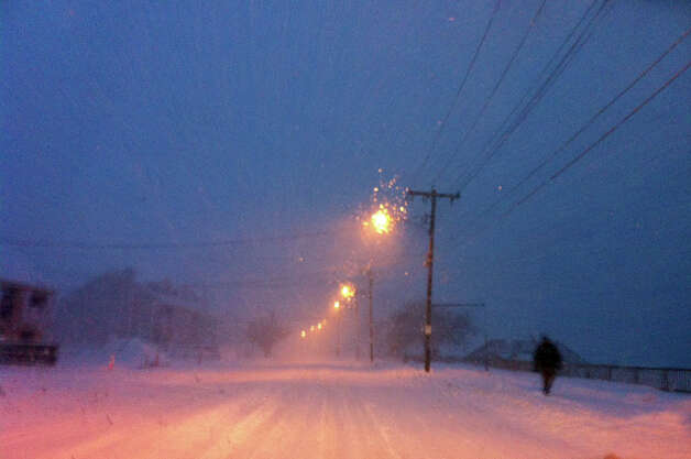 A lone pedestrian walks along Beach Street while a blizzard pounds the region in West Haven, Conn. on Friday evening February 8, 2013. Photo: Christian Abraham / Connecticut Post
