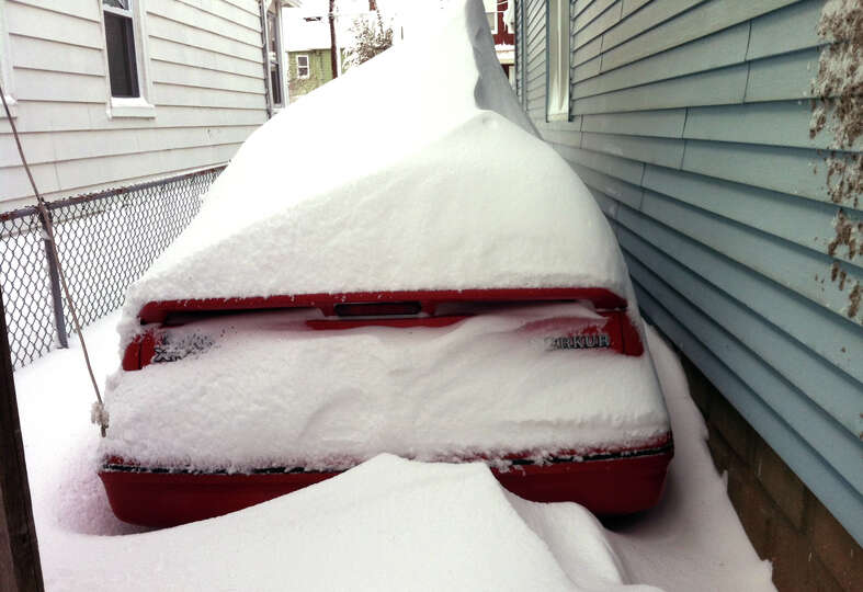 Snow almost buries a vehicle after a blizzard pounded the region in West Haven, Conn. on Saturday Fe