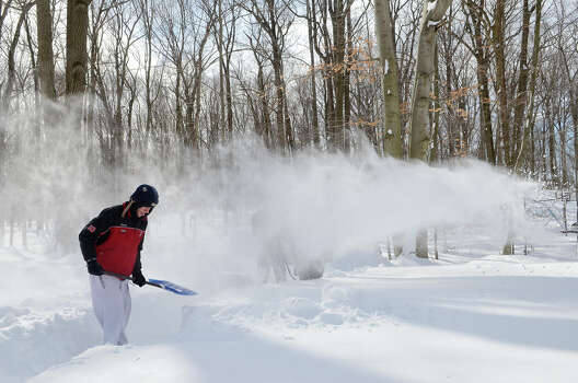 Dan Silvestri, 17, helps clear a path to his family's backyard wood pile in Southport, CT on Sat., Feb. 9, 2013, following a blizzard that dumped up to three feet of snow across the state. Silvestri's dad, Peter Silvestri, operates a snowblower in the background. Photo: Shelley Cryan / Shelley Cryan for the CT Post/ freelance Shelley Cryan