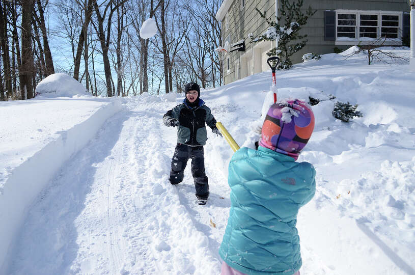 Twins Luke and Poppy Mituski play an improvised game of baseball in the snow in their driveway in So