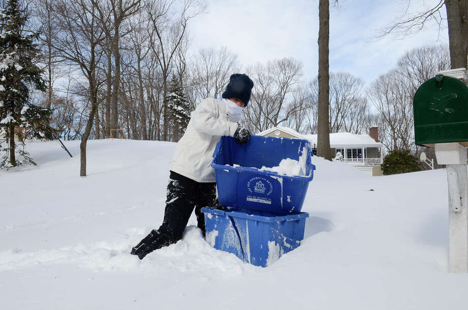 Sydney McArthur, 16, Fairfield, helps bring in the recycling bins at a friend's house in Southport, CT on Sat., Feb. 9, 2013, following a blizzard that dumped up to three feet of snow across the state. She wanted to get them in before the plows came. Photo: Shelley Cryan / Shelley Cryan for the CT Post/ freelance Shelley Cryan