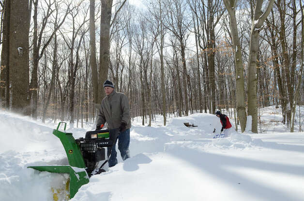 Peter Silvestri navigates a snowblower in his yard in Southport, CT on Sat., Feb. 9, 2013, following a blizzard that dumped up to three feet of snow across the state. Silvestri needed to clear a path to his backyard wood pile, near where his son Dan Silvestri is shoveling. Photo: Shelley Cryan / Shelley Cryan for the CT Post/ freelance Shelley Cryan