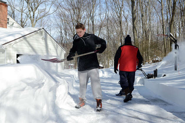 Jake Tymon, 14, helps neighbors shovel out their driveway  in Southport, CT on Sat., Feb. 9, 2013, following a blizzard that dumped up to three feet of snow across the state. Photo: Shelley Cryan / Shelley Cryan for the CT Post/ freelance Shelley Cryan