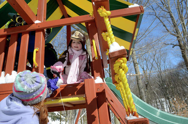 Molly Coccaro, 7, hands a roll of string to her sister Caroline Coccaro, 9, in their backyard playset as they make the best of a snowy day in Southport, CT on Sat., Feb. 9, 2013, following a blizzard that dumped up to three feet of snow across the state. Photo: Shelley Cryan / Shelley Cryan for the CT Post/ freelance Shelley Cryan