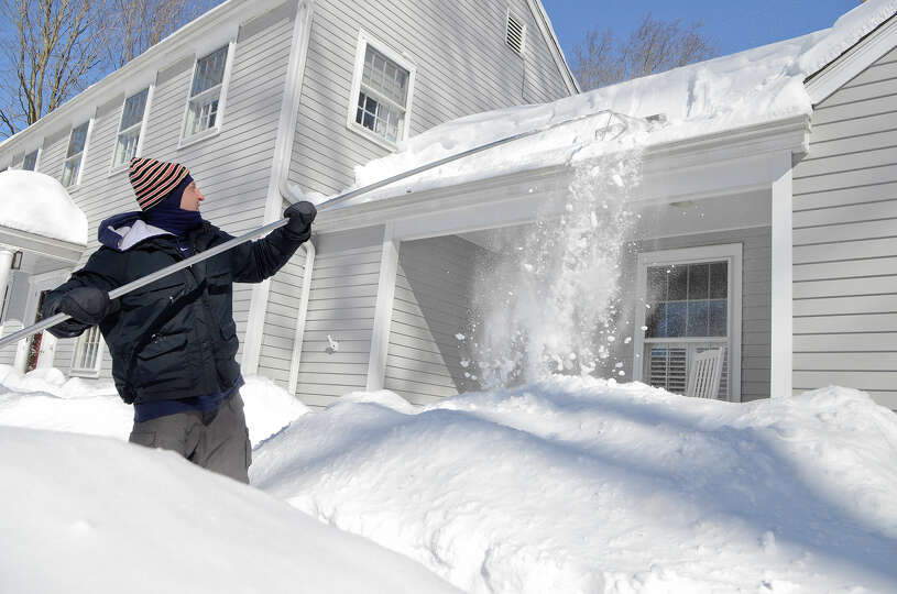 T.R. Coccaro uses a roof rake on his home as he contends with the snow in Southport, CT on Sat., Feb