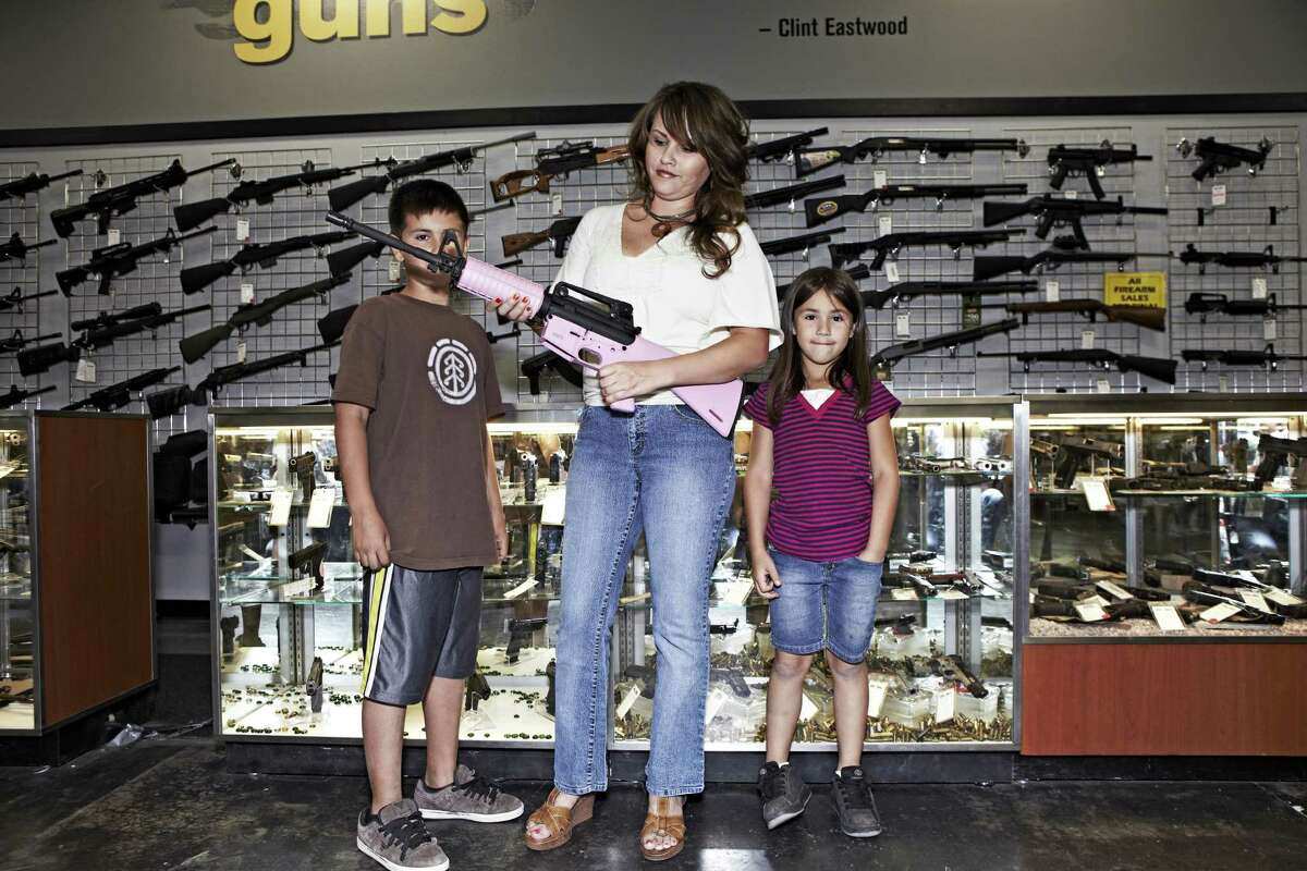 A woman with her children holds a pink AR-15 at the Gun Showroom in Phoenix.