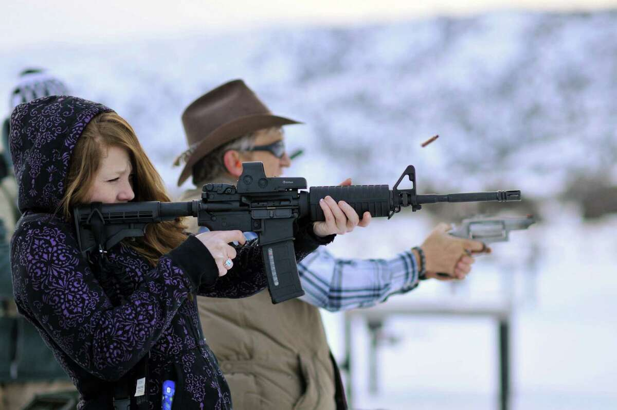 A young woman fires a semi-automatic assault rifle with a high-capacity magazine at a shooting range. Gun control advocates are trying to outlaw these types of magazines.