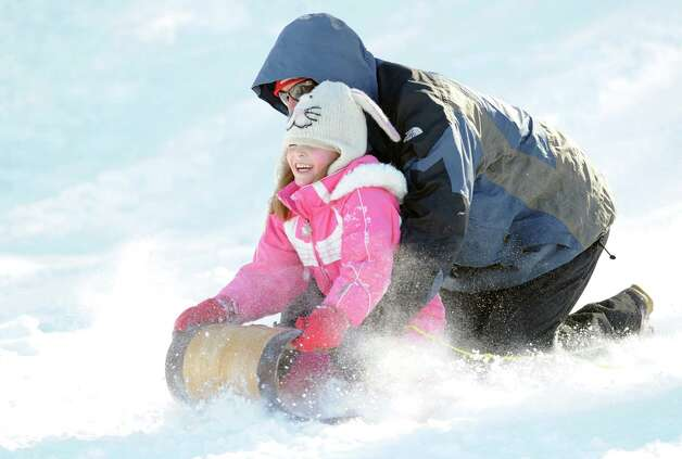 Tito Citarella attempts to steer his toboggan as his daughter, Claire, 6,  holds onto the front of the sled as the pair took advantage of the snow sledding on the hill near the Western Greeenwich Civic Center during the aftermath of the blizzard that hit Greenwich, Saturday, Feb. 9, 2013. Photo: Bob Luckey / Greenwich Time
