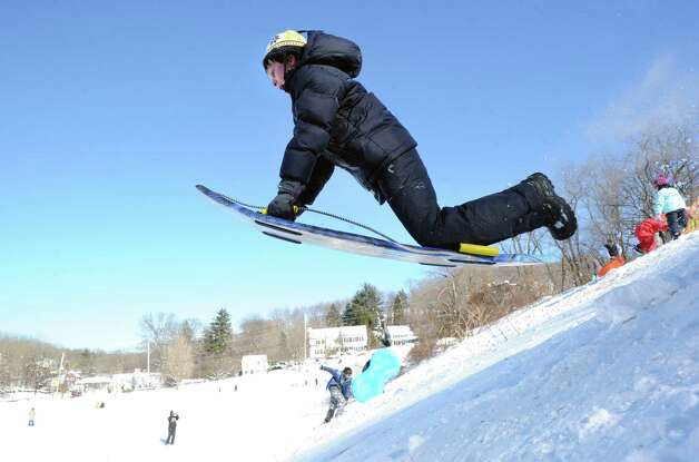 Josh Frumin, 10, of Greenwich, uses his sled to jump over a ramp on the hill near the Western Greeenwich Civic Center during the aftermath of the blizzard that hit Greenwich, Saturday, Feb. 9, 2013. Photo: Bob Luckey / Greenwich Time