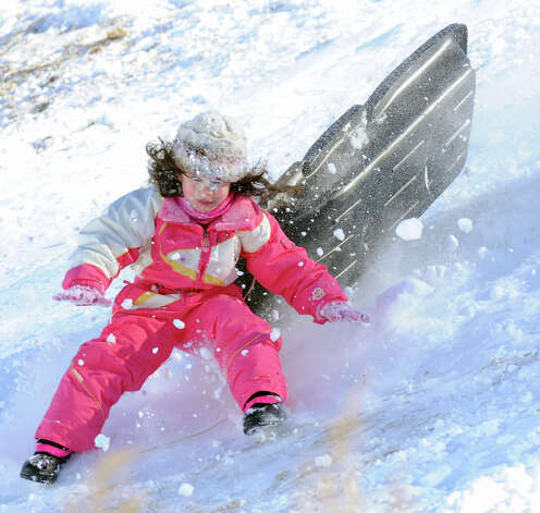 Emily Duarte, 5, of Glenville, wipes out as she jumps over a ramp on the hill near the Western Greeenwich Civic Center during the aftermath of the blizzard that hit Greenwich, Saturday, Feb. 9, 2013. Photo: Bob Luckey / Greenwich Time