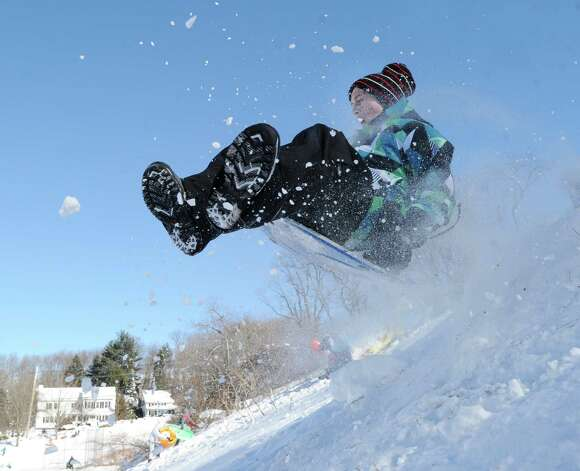 A boy on a sled jumps over a ramp on the hill near the Western Greeenwich Civic Center during the aftermath of the blizzard that hit Greenwich, Saturday, Feb. 9, 2013. Photo: Bob Luckey / Greenwich Time