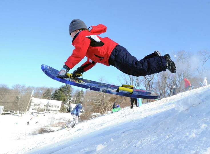 A boy on a sled jumps over a ramp on the hill near the Western Greeenwich Civic Center during the af