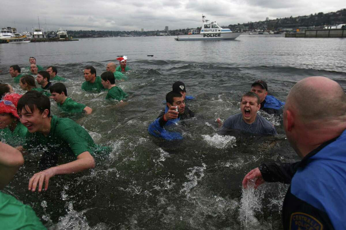Plungers dip into the chilly water of Lake Union during the Special Olympics Washington Polar Plunge on Saturday, February 9, 2013 at South Lake Union Park in Seattle. Nearly 600 plungers participated in the event, part of a fundraiser for Special Olympics Washington.