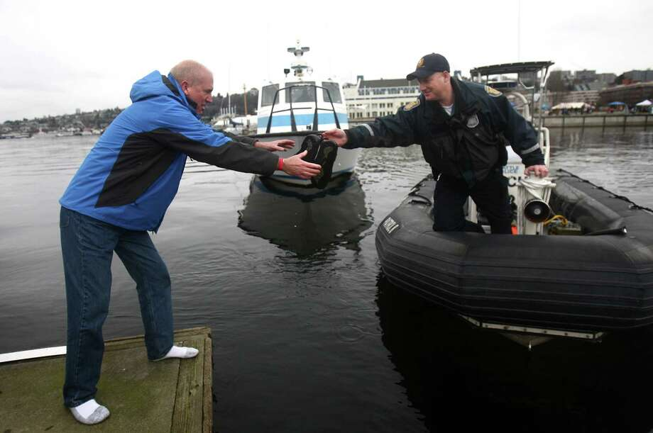 King County Sheriff John Urquhart, left, is handed the shoes he lost in Lake Union while participating in the Special Olympics Washington Polar Plunge on Saturday, February 9, 2013 at South Lake Union Park in Seattle. The shoes were retrieved from the lake by Seattle Police Officer Scott McGlashan. Nearly 600 plungers participated in the event, part of a fundraiser for Special Olympics Washington. Photo: JOSHUA TRUJILLO, SEATTLEPI.COM / SEATTLEPI.COM