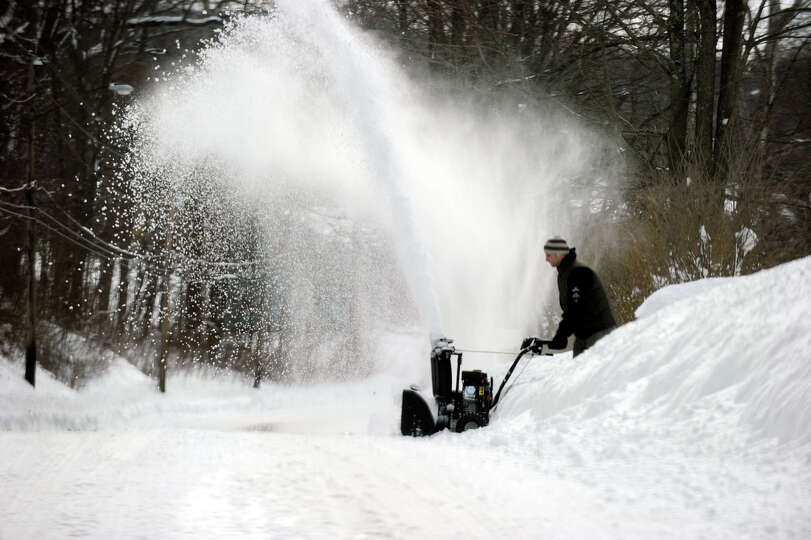 Max Veiga of Danbury uses a snowblower to clean his driveway on Coalpit Road in Danbury, Saturday, F