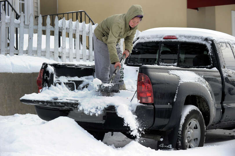 Jesse Wong cleans out the snow in the back of her truck on Grassy Plain Road in Bethel, Conn. Saturd