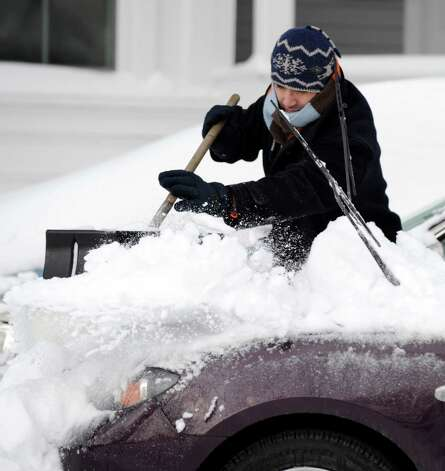 Italo Venegas cleans off his off his car on Grand Street in Bethel, Conn. Saturday, Feb. 9, 2013. A blizzard dumped almost two feet of snow on the Danbury area Friday and early Saturday morning. Photo: Carol Kaliff / The News-Times