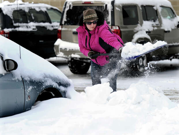 Michele Conderino of Bethel digs out her friends car in a parking lot on Greenwood Ave. in Bethel, Conn. Saturday, Feb. 9, 2013. She says someone dug her out so she is passing on the favor. A blizzard dumped almost two feet of snow on the Danbury area Friday and early Saturday morning. Photo: Carol Kaliff / The News-Times