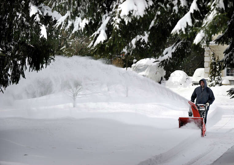Tony Sousa, of Bethel, snowblows the driveway of his home on Route 53 in Bethel, Conn. Saturday afte
