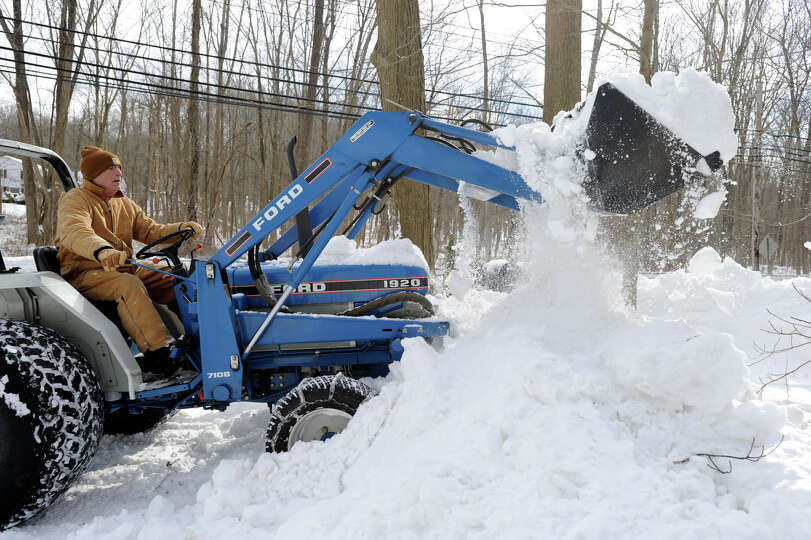 Roger Faille of Redding plows his neighbor's driveway on Route 107 in Redding, Conn. Saturday, after