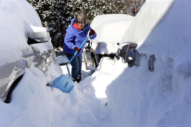 Joan Rothfuss, shovels out her cars on Karen Blvd. in Newtown, Conn. aftera blizzard dumped almost t