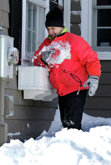 Mark Forlenzo, cleans snow out of the flower boxes around his home on Glover Avenue in Newtown after